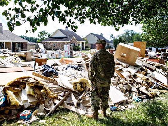 """Chris Daves, a National Guardsman, surveys the damage from a friend's yard. He's there to help and listen, """"We're fellow armyman, that's what we do."""" Watson, LA."""