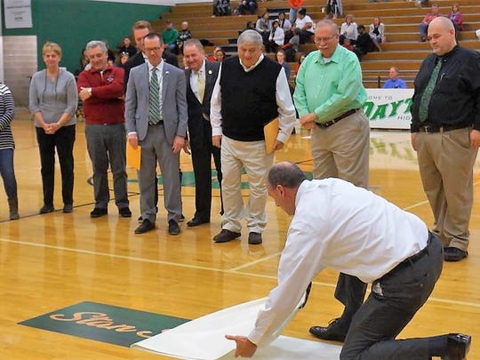 Stan Steidel (black sweater vest) watches his logo unfold during the ceremony Jan. 13, 2018 at Dayton HS.