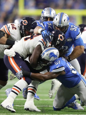 Lions linebacker Josh Bynes (57) and defensive tackle Haloti Ngata tackle Bears running back Jordan Howard on Sunday, Dec. 11, 2016 at Ford Field.