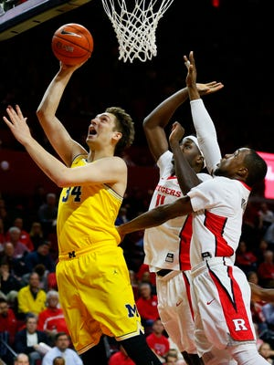 Feb 22, 2017; Piscataway, NJ, USA; Michigan Wolverines forward Mark Donnal goes to the basket against Rutgers Scarlet Knights forward Eugene Omoruyi (11) and guard Mike Williams (5) during the first half at Louis Brown Athletic Center.