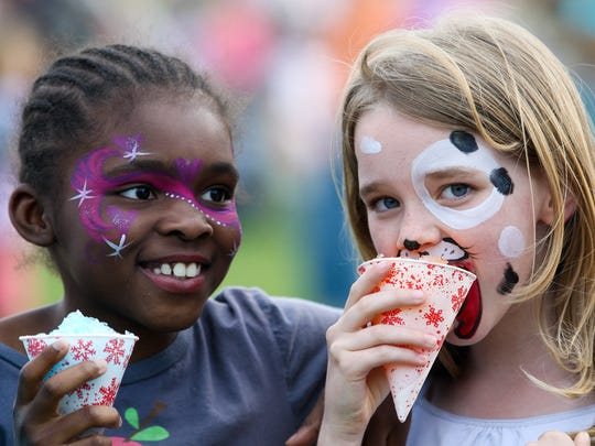 Camille Reeves (left), 9, and Marie Stack, 8, of Greenville enjoy water ice at the Wilmington Flower Market in 2011.