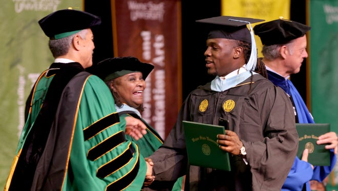 Wayne State president M. Roy Wilson shakes hands with Lions running back Joique Bell after giving him his master's degree in sports administration from the College of Education during ceremonies at the Matthaei Physical Education Center on the campus of WSU in Detroit on Saturday, Dec.10, 2016.
