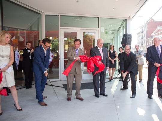 Using swords instead of the more traditional scissors, Cincinnati Shakespeare Company executive director Jay Woffington (center L) and producing artistic director Brian Isaac Phillips (center R) do the ribbon-cutting honors for the $17.5 million Otto M. Budig Theater, the new home of CSC.