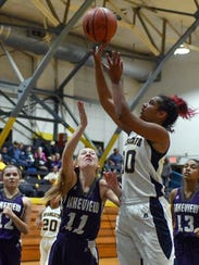 Battle Creek Central's Arieonna Ware (30) drives the basket during game action earlier this season.