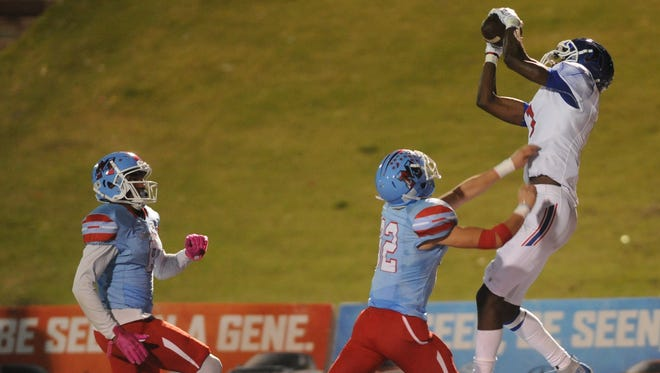 Cooper receiver Myller Royals, right, hauls in a 20-yard touchdown catch as Lubbock Monterey's Justin Jones, center, and James Langston defend. The catch cut Monterey's lead to 20-7 with 8:30 left in the second quarter. Monterey won the District 4-5A opener Friday, Oct. 13, 2017 at Lowrey Field in Lubbock.