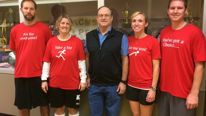 Kate Collins physical education teachers, from left, John Hull, Lori Aleshire, Dave Huffer, Julie Stevens, and David Durham. The red shirts all include phrases frequently said by Huffer, who is retiring after 38 years at the school.