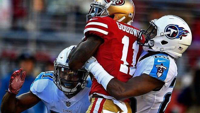 Titans safety Kevin Byard (31) and cornerback Adoree' Jackson (25) tackle 49ers wide receiver Marquise Goodwin (11) in the first quarter at Levi's Stadium Sunday, Dec. 17, 2017 in Santa Clara, Calif.
