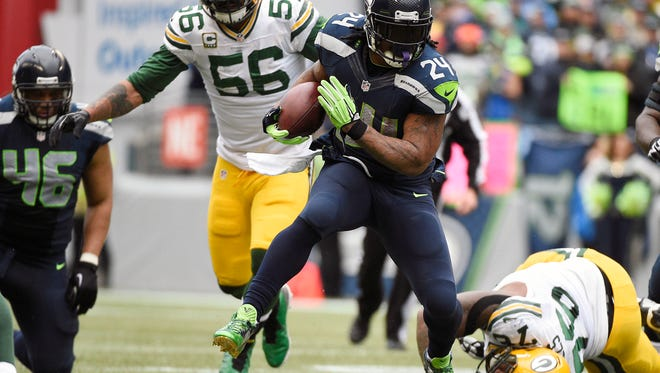 January 18, 2015; Seattle, WA, USA; Seattle Seahawks running back Marshawn Lynch (24) runs the ball ahead of  Green Bay Packers outside linebacker Julius Peppers (56) and defensive end Mike Daniels (76) during the second half in the NFC Championship game at CenturyLink Field.