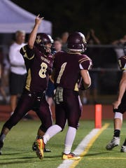 Arlington's Austin Heck celebrates a touchdown with teammates during a Sept. 2016 game against rival Ketcham.