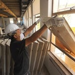 Ruben Aviles sends a light panel down a garbage chute as he and others remodel the fifth floor of Ventura City Hall North in June.