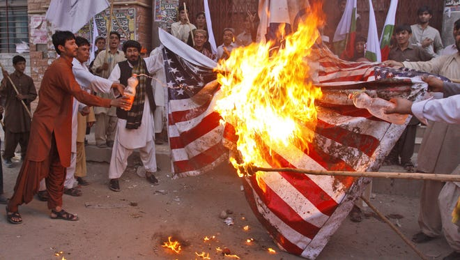 Protesters from the religious tribal party Awami Majlis-e-Amal burn a representation of a U.S. flag during an anti-NATO protest in Quetta, Pakistan, on July 13, 2012.