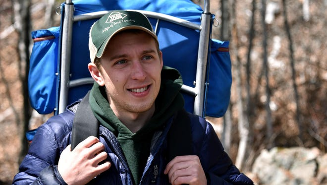 """Gabe Prizer,22, a senior at Northern Michigan University in Marquette, Mich., has lived in a shelter in the woods since August, 2015. He pauses to speak with hikers Friday, April 22,, 2016. """"There is a lot of activity along this trail,"""" said Prizer. A native of Troy, Mich, Prizer simply wanted to challenge himself, and build his shelter in a park overlooking the Dead River empoundment a mile from the university."""