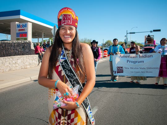 Ashley Terry, NMSU's Miss Native American, holds candy to give to children as she walks down University Avenue with other members of the American Indian Program as part of Saturday's homecoming parade.