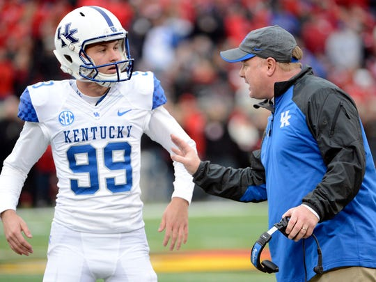 Austin MacGinnis talks with coach Mark Stoops during a game.