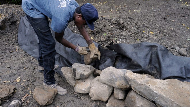 Isiah Hawley, 18, a Nubian Directions student and city resident, builds a retaining wall for a rain garden in Poughkeepsie.