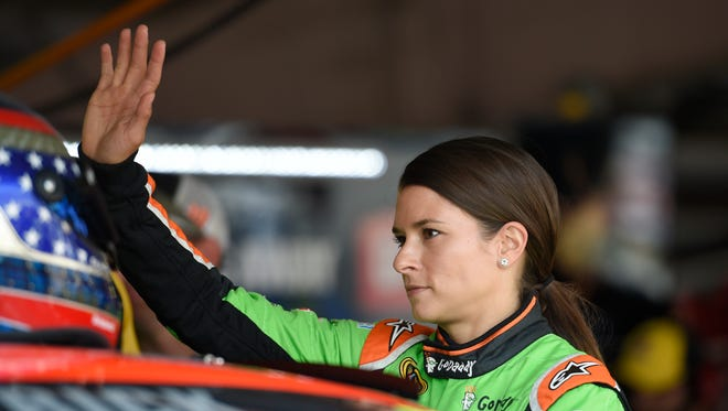 Danica Patrick waves in the garage area before practice for Sunday's NASCAR Sprint Cup series auto race, Saturday, May 30, 2015, at Dover International Speedway in Dover, Del.