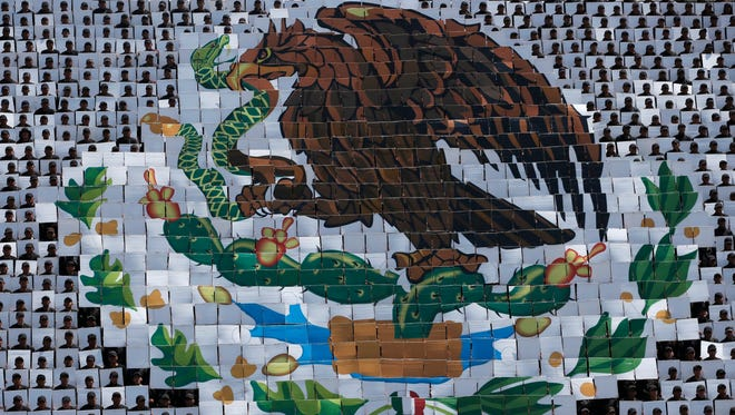 Hundreds of military troops hold cards making a mosaic depiction of the Mexican coat of arms, an eagle catching a serpent while standing atop a cactus, during a review of the troops that will march in the Independence Day parade. Thousands will gather in Mexico City's main square known as the Zocalo on Friday for a massive military parade to commemorate Mexico's independence from Spain.