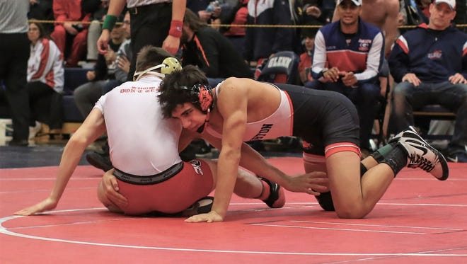 Aiden Brown (right) and his Brighton wrestling teammates will begin postseason action Wednesday in the district at Pinckney.