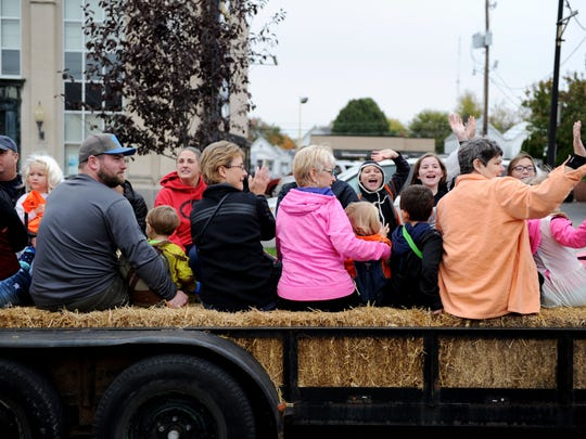 People wave while on a hay ride during Halloween on Franklin Street last year.