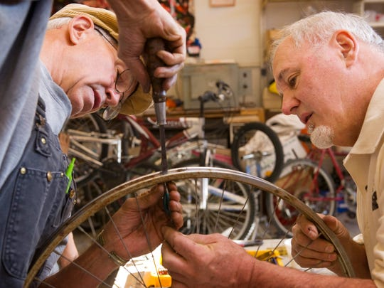 John Leavitt, left, and Pete Emery replace a spoke on a bicycle rim at Patchwork Central's bike shop.