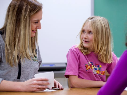 Oakland City Elementary School teacher Lauren Schmidt, left, ask her student, Julia Harrison, 9, why all of her pictures seem to have unicorns in them.