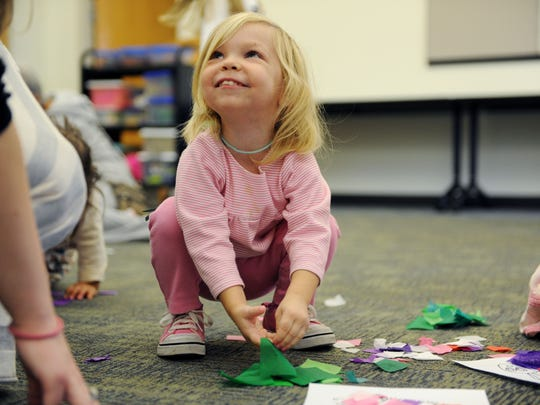 Miriam Wenderoth smiles while while making a caterpillar with tissue paper during a past preschool story time at the Evansville Vanderburgh Public Library Oaklyn Branch.