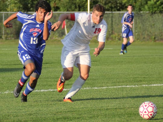 St. Clair's Nick Ball and Port Huron High's Will Kriewall race for the ball in the MAC Gold Varsity Soccer matchup between Port Huron and St. Clair High Schools.