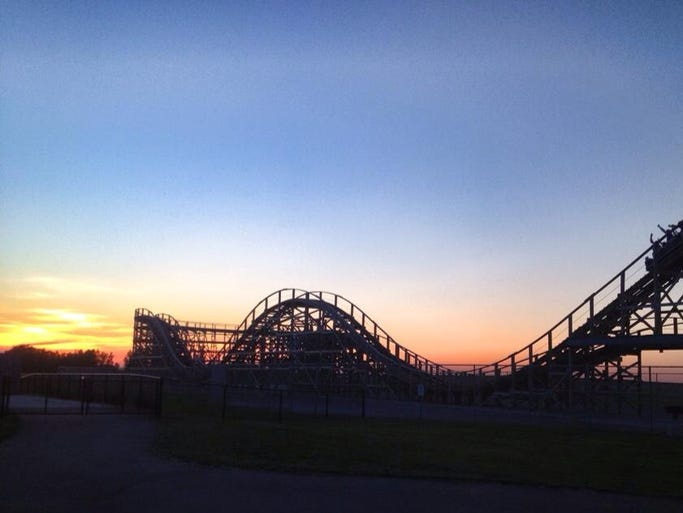 A view of the sunset over the Zippin' Pippin' at Bay Beach Amusement park on June 26, 2014.