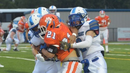 Columbia Academy running back Colton Sandifer is tackled by a pair of Sacred Heart defenders on Friday night at Sacred Heart.