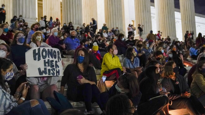 People gather at the Supreme Court Friday in Washington, after the Supreme Court announced that Supreme Court Justice Ruth Bader Ginsburg has died of metastatic pancreatic cancer at 87.