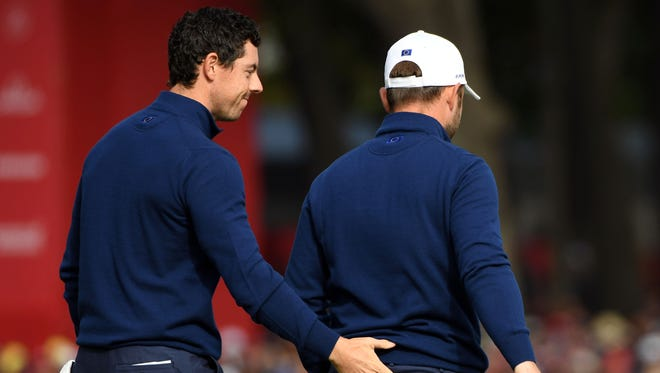 Rory McIlroy of Northern Ireland walks with  Andy Sullivan of England on the 12th green in the morning foursome matches during the 41st Ryder Cup at Hazeltine National Golf Club.