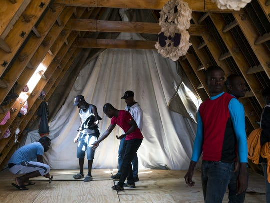 Haitian migrants help build an addition to the Desayunador