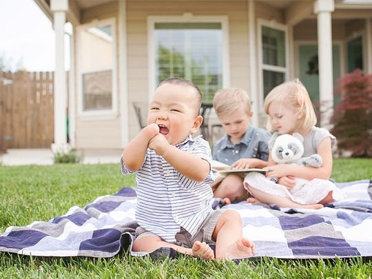 Oliver Kanallakan, who was adopted from China, sits outside his new home in Visalia with his new siblings Jane and Sawyer.