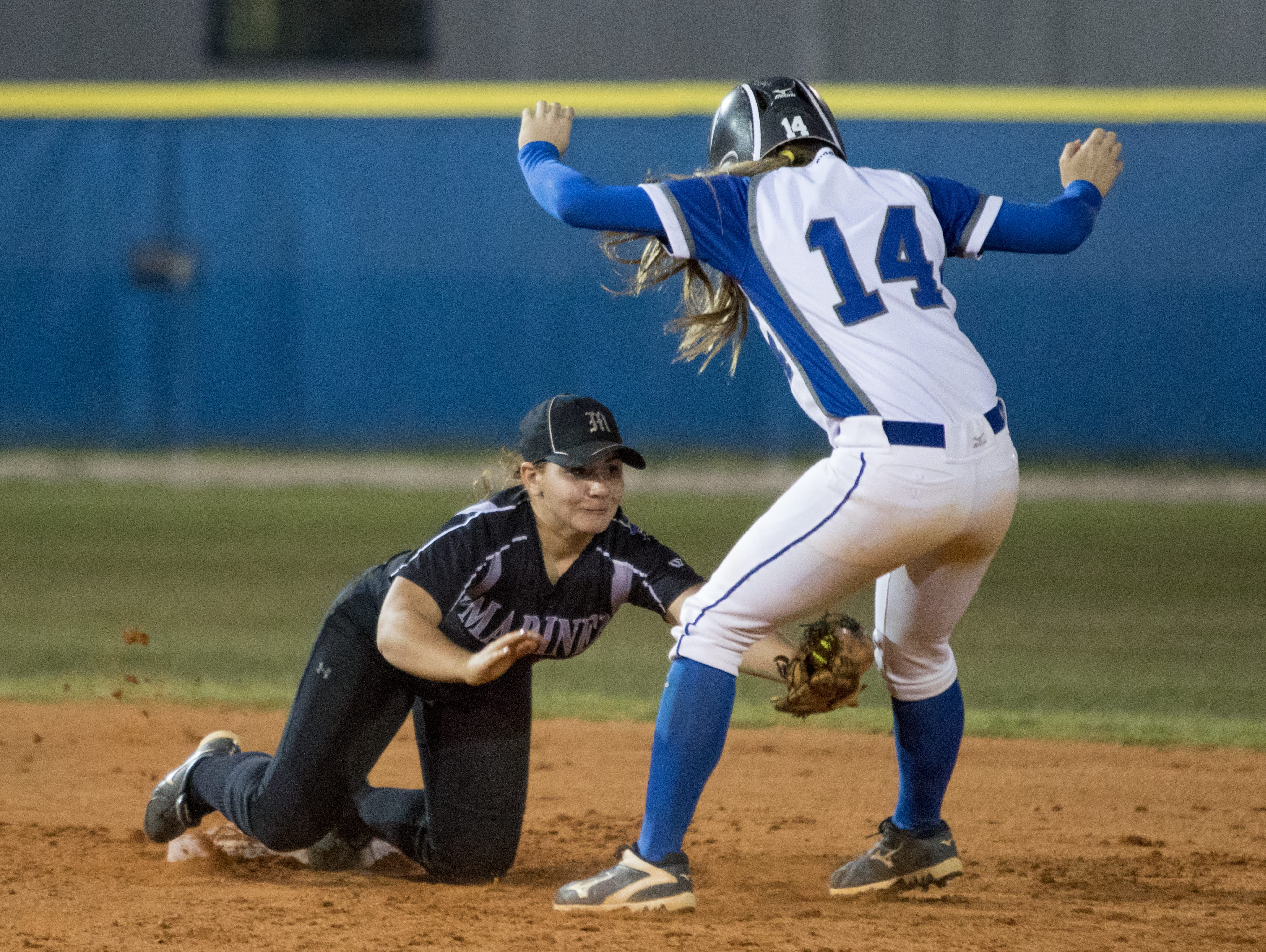 Barron Collier H.S.'s Chloe Freischmidt (14) tries to avoid the tag of Mariner H.S. second baseman Ari Sosa (6) during a failed attempt to steal second in the class 6A regional softball quarterfinal game at Barron Collier High School in Naples, FL on Wednesday, April 20, 2016. (Photo by Gregg Pachkowski/Special to the Daily News)