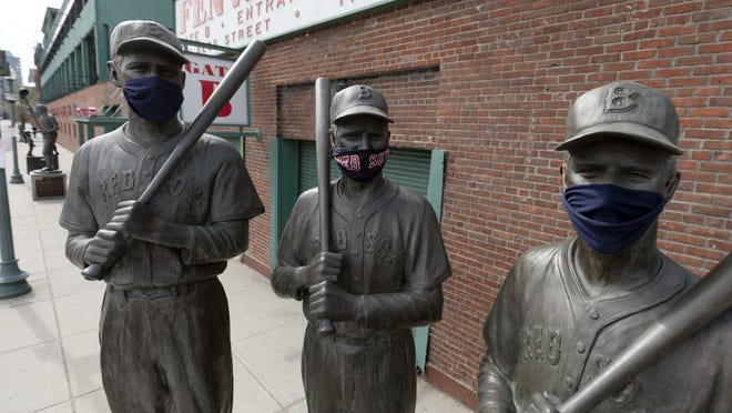 Statues of former Boston Red Sox greats, from left, Ted Williams, Bobby Doerr and Johnny Pesky wear protective masks outside Fenway Park on April 17.