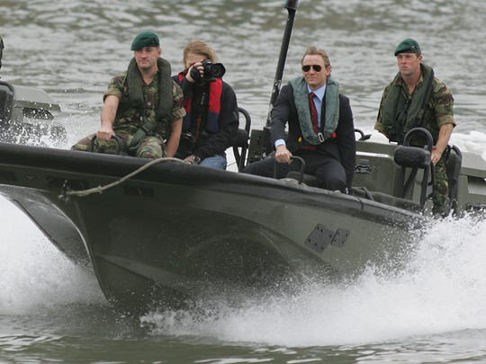 """File - In this Friday Oct. 14, 2005 file photo, new James Bond, Daniel Craig, 2nd right, arrives by boat for his press unveiling in London. Craig's selection was revealed as he was whisked down the River Thames aboard a military Rigid Raider boat. """"Spectre,"""" which has its World Premiere Monday Oct. 26, 2015, in London in front of Prince William, his wife Kate and brother Prince Harry, is the fourth, and potentially last time, he will reprise his role as the British secret agent. (AP Photo/Alastair Grant, File)"""