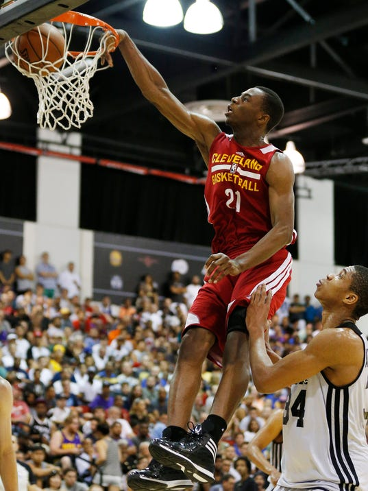 FILE - In this July 11, 2014, file photo, Cleveland Cavaliers' Andrew Wiggins, the No. 1 overall pick in the NBA draft, dunks against the Milwaukee Bucks during an NBA summer league basketball in Las Vegas. Wiggins will sign his rookie contract with the Cavaliers, an agreement that would prevent any potential trade involving the small forward from being completed for 30 days, a person familiar with the negotiations says. (AP Photo/John Locher, File)