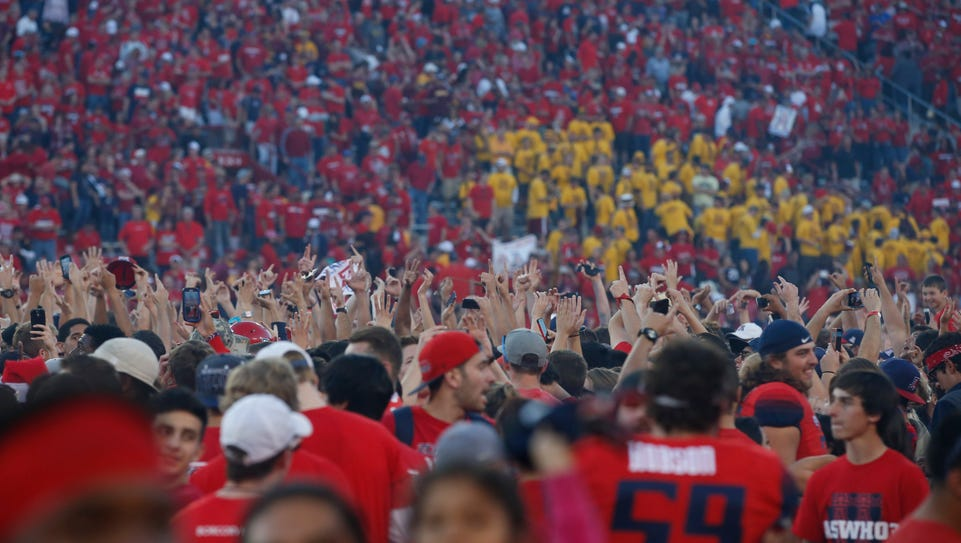 Arizona fans storm the field after winning the Territorial