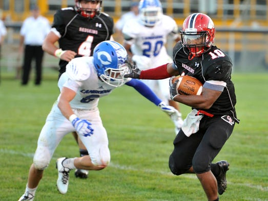 Coshocton Redskins senior Dom Johns stiff arms Cambridge's Riley Hayhurst on his way to the end zone for the Skins first touchdown of the season Friday night.