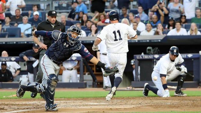 New York Yankees left fielder Brett Gardner (11) crosses the plate as Minnesota Twins catcher Kurt Suzuki (8) misses the ball during the second inning Friday at Yankee Stadium in New York.