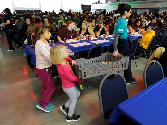 Cynthia Kneip (right) gets help carrying a tray of food from her daughters, Becca (left), 8, and Faith (center), 5, during the HEB Feast of Sharing on Tuesday, Dec. 6, 2016, at the Abilene Civic Center.