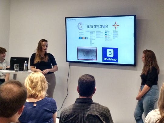 Interns Victoriya Tarakanova and Sophie Bohr present what they've been working on to other interns and SafeNet staff while fellow intern Daniel Anderson runs the slides.