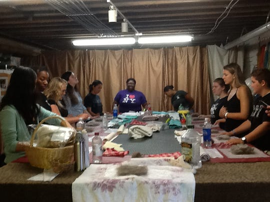 First day of class, Aug. 31, 2015. Students in Professor Sprangel's Sustainability and Strategy in Business Decisions class at Mary Baldwin College line up around the table at Jacenich's studio to get hands-on experience working with wool, a sustainable material.
