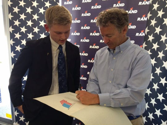 "U.S. Sen Rand Paul autographs a copy of the Constitution for 16-year-old Logan Dodson during a campaign stop Thursday in Henderson. Dodson is vice president of the Henderson County Young Republicans. ""We're trying to get all of the politicians that we meet to sign our copy of the Declaration of Independence, the Constitution and the Bill of Rights — important American documents — as a promise to us and the state of Kentucky that they will do their best to preserve it in Washington,"" he said."