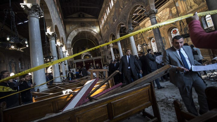 Egyptian security forces inspect the scene of a bomb