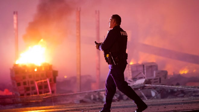 A police officer walks by a blaze Monday night after rioters plunged part of Baltimore into chaos, torching a pharmacy, setting police cars ablaze and throwing bricks at officers.