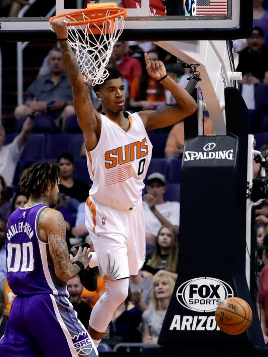 Phoenix Suns forward Marquese Chriss (0) signals to a teammate after dunking as Sacramento Kings center Willie Cauley-Stein (00) defends during the first half of an NBA basketball game, Wednesday, March 15, 2017, in Phoenix. (AP Photo/Matt York)