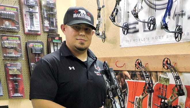 Chuck Turner holds a compound bow next to a display at Rockin' R Archery located at 4301 E. Pine St. Churck and his father Rick opened the shop in the old Sandy's Gas Station location on Deming's east side.
