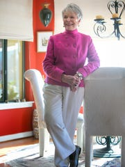 Peg Tigue wears a double-breasted hot pink Doncaster jacket with pink turtle neck blouse and white pants.