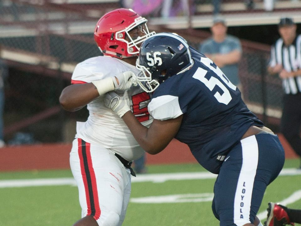 Orchard Lake St. Mary's linebacker Ralph Holley tangles with Detroit Loyola defender Teron Johnson at Hazel Park on Friday.